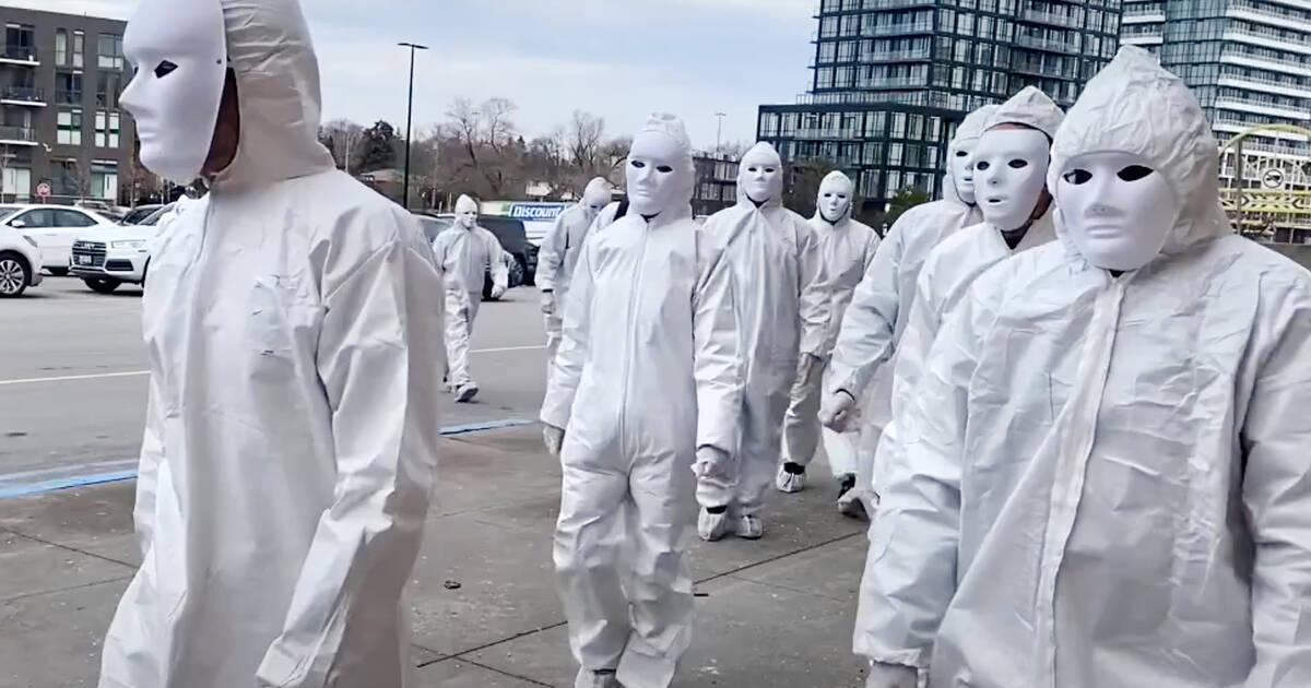 白い服を着た仮面の人々がトロントのモールを襲撃し、COVIDワクチンに抗議した
