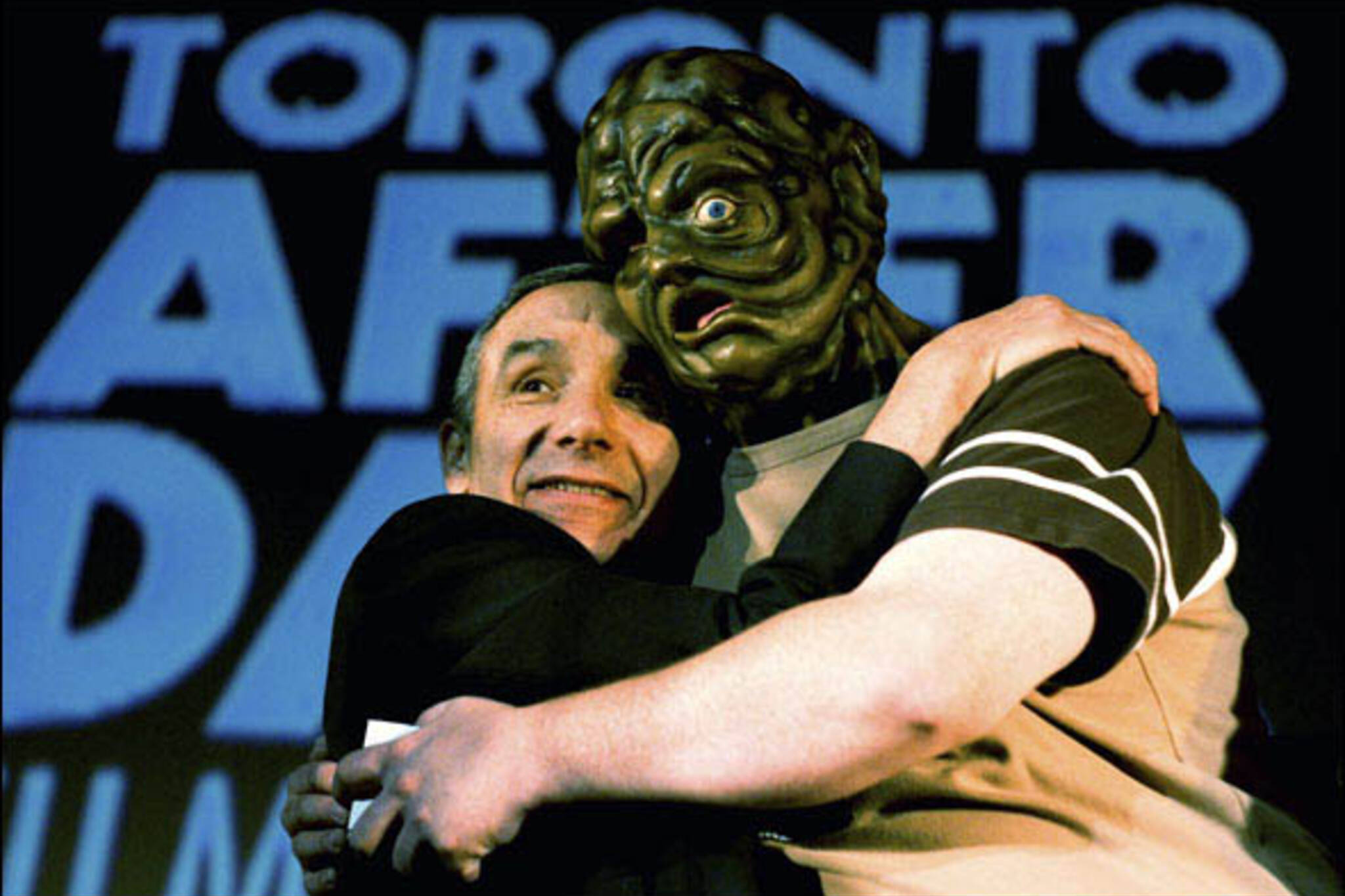 Director Lloyd Kaufman embraces a ghoulish creature on stage after the Toronto premiere screening of Poultrygeist: Night of the Chicken Dead at The Bloor Cinema during the Toronto After Dark Film Festival.